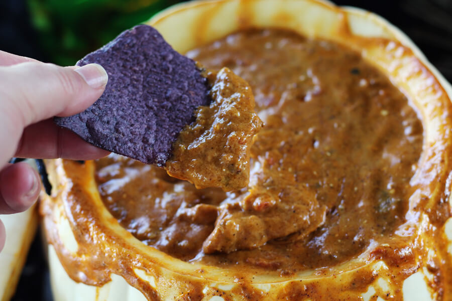 A blue corn tortilla chip dipped into chili cheese RO*TEL dip