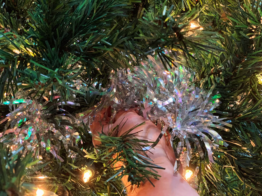 Create the illusion of a fuller tree and a soft glow by tucking tinsel garland pieces in the center of the Christmas tree.