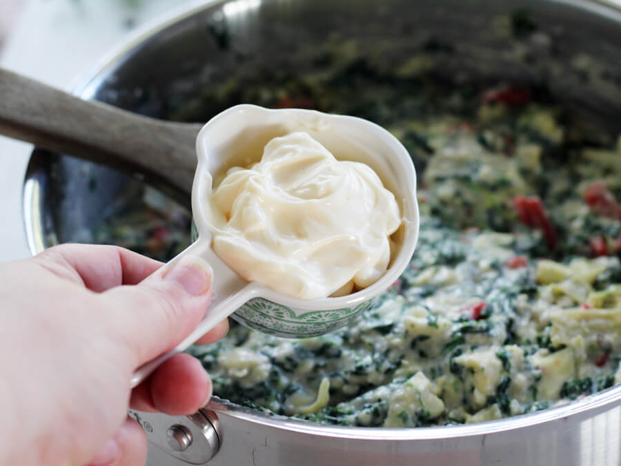 Creamy mayonnaise being added to spinach artichoke dip