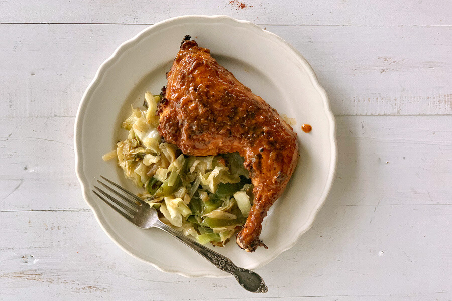 A plate with a grilled, sauced chicken quarter served with fried cabbage