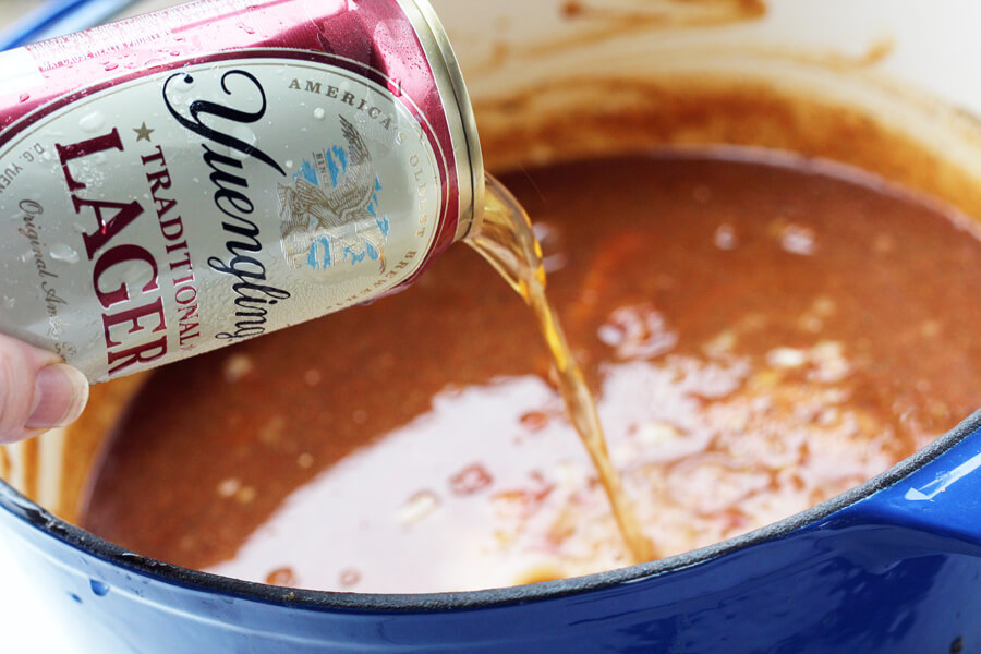 A can of beer being poured into a pot of barbecue sauce