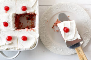 Cherry cake in a baking pan next to a plate with a piece of cake.