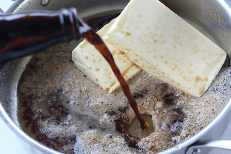 A bottle of dark stout beer being poured into a sauce pan with butter