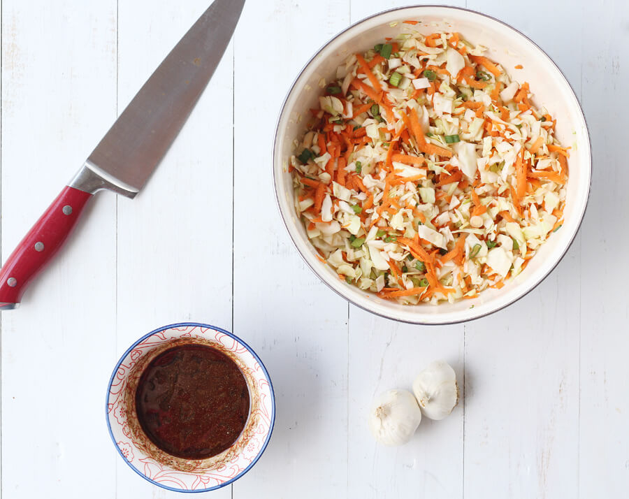 A bowl of chopped cabbage with carrots and onions next to a bowl of soy sauce and seasonings