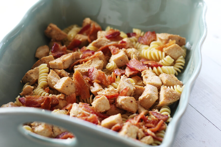 Chunks of cooked chicken, bacon, and rotini pasta in a baking dish part of recipe preparation.