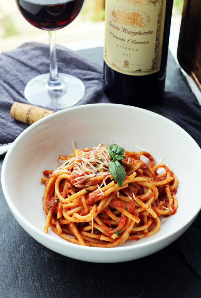 Pasta + wine = happy me. I can think of NO better way to celebrate National Wine Day (or...Tuesday), than with this appetizing recipe for Bucatini Pasta. Get ready to fall in love with this easy homemade chianti sauce that is slow-simmered with roasted garlic, Italian Chianti wine, olives, and more.