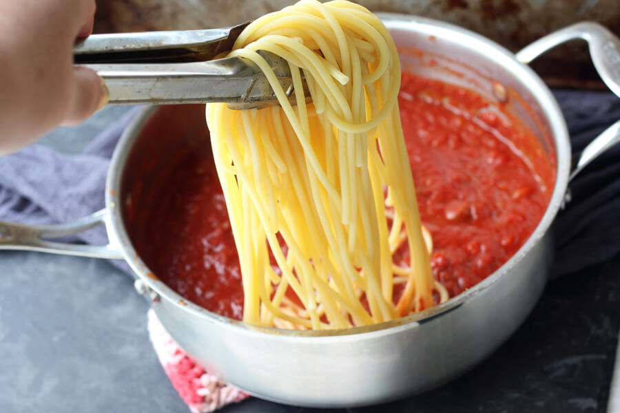 Bucatini pasta being added to a pan of chianti tomato sauce