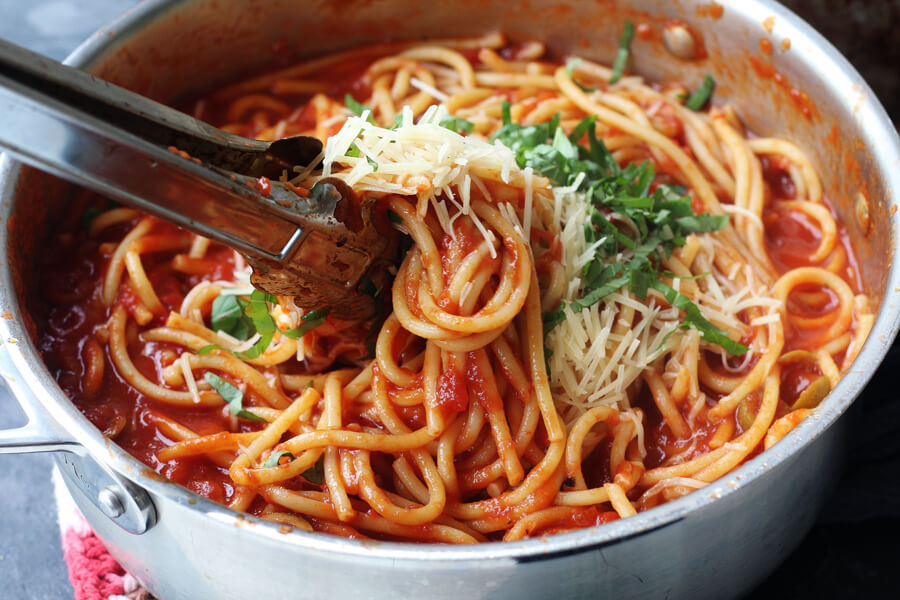 A sauce pan with bucatini pasta swirled with chianti tomato sauce, shredded parmesan cheese, and fresh chopped basil.