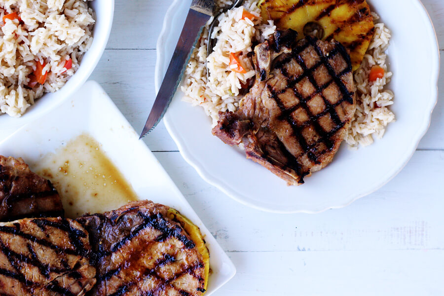 Dinner is served! Tender, pineapple soy pork chops served with grilled slices of pineapple on a bed of rice. Yum!