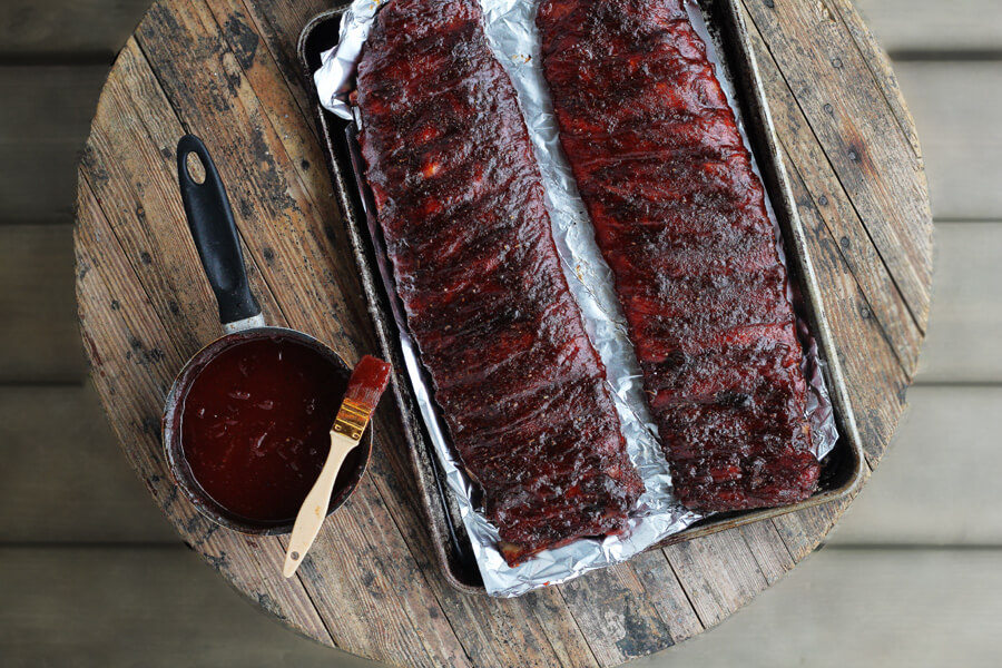 This recipe for St. Louis Style BBQ Ribs is lip-smacking good. Slow roasted with charcoal, this rib recipe features a homemade spice rub and sauce.