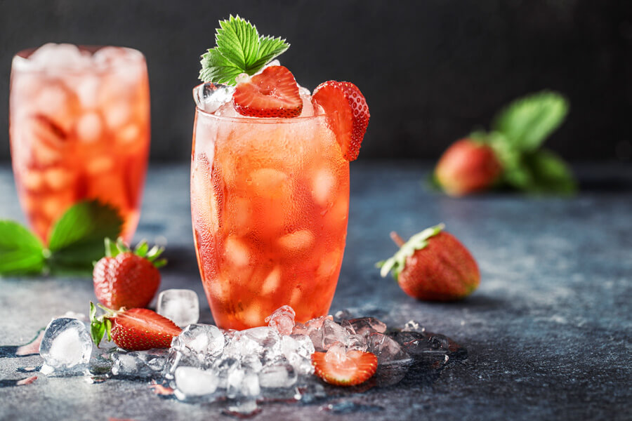 Made with fresh strawberries, sugar, lemon, and mint and mixed with club soda and light rum, this refresing strawberry cocktail will be a hit at your next party!#rumcocktails #strawberrycocktails