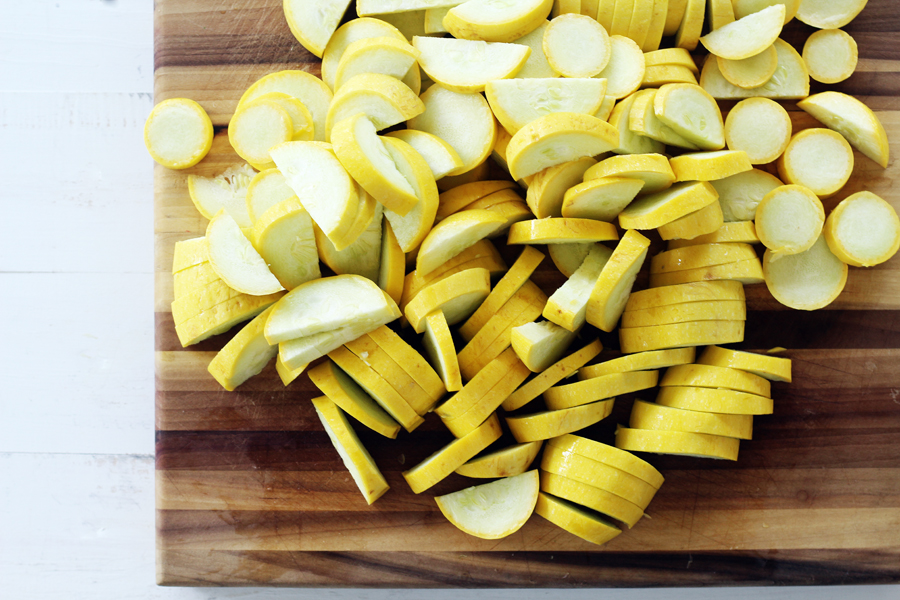 Sliced yellow squash on a wooden cutting board.