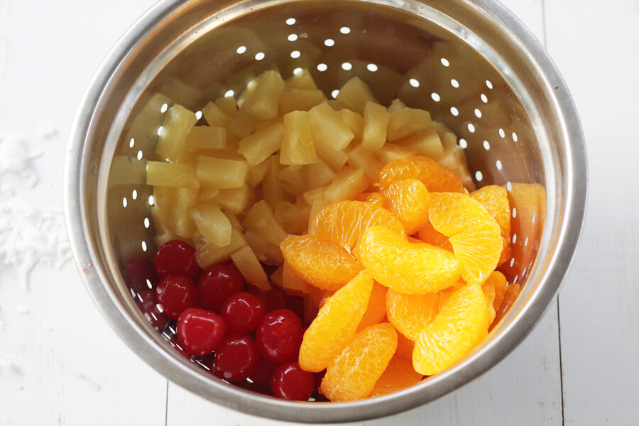 A colander with pineapple chunks, maraschino cherries, and mandarin oranges, ingredients for ambrosia salad