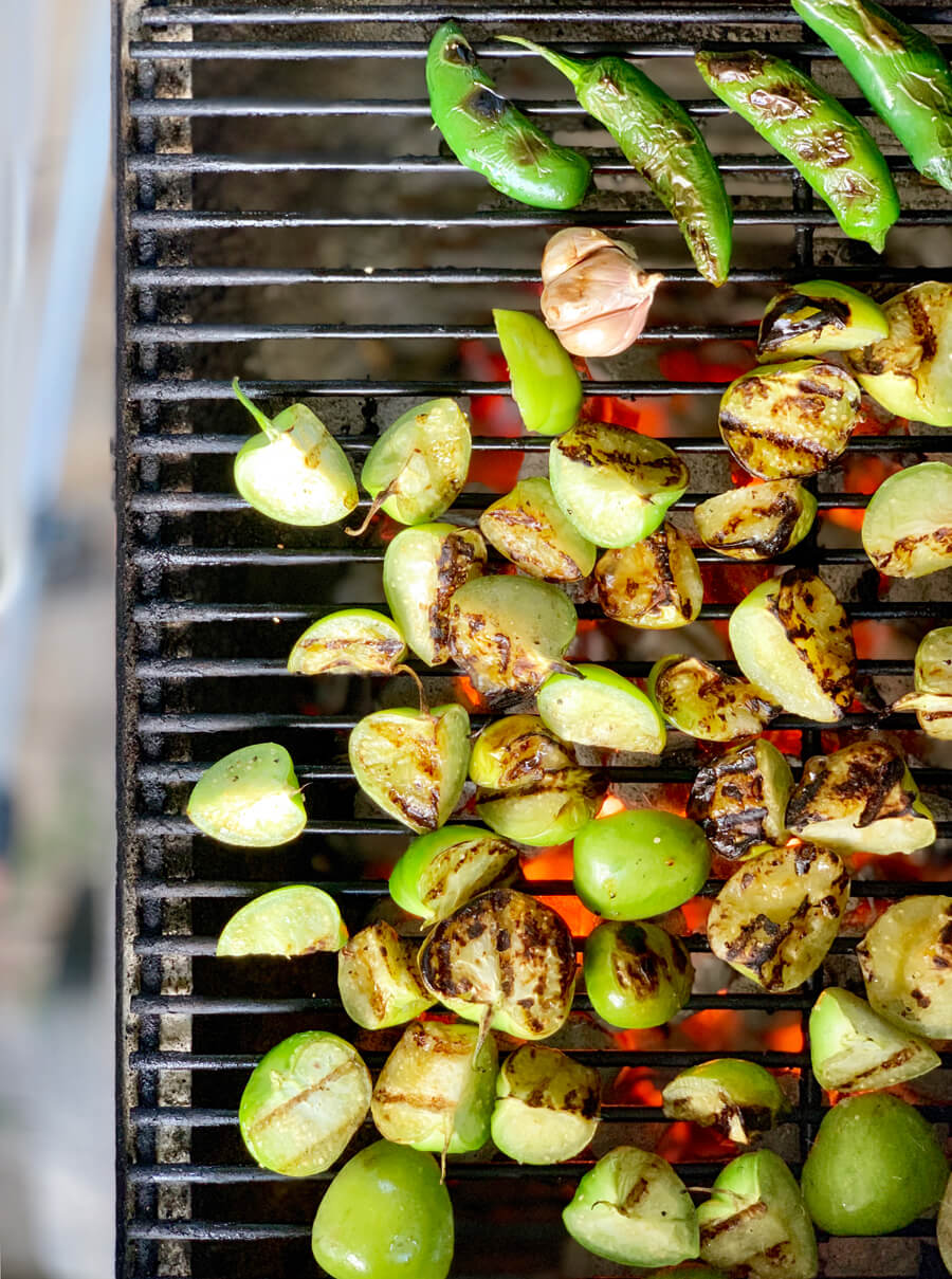 Tomatillos, onions, jalapenos and garlic on a hot charcoal grill