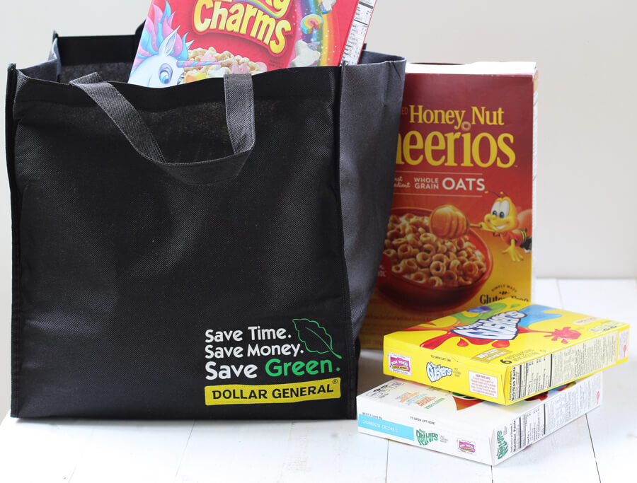 A shopping bag filled with boxes of cereal and kids snacks
