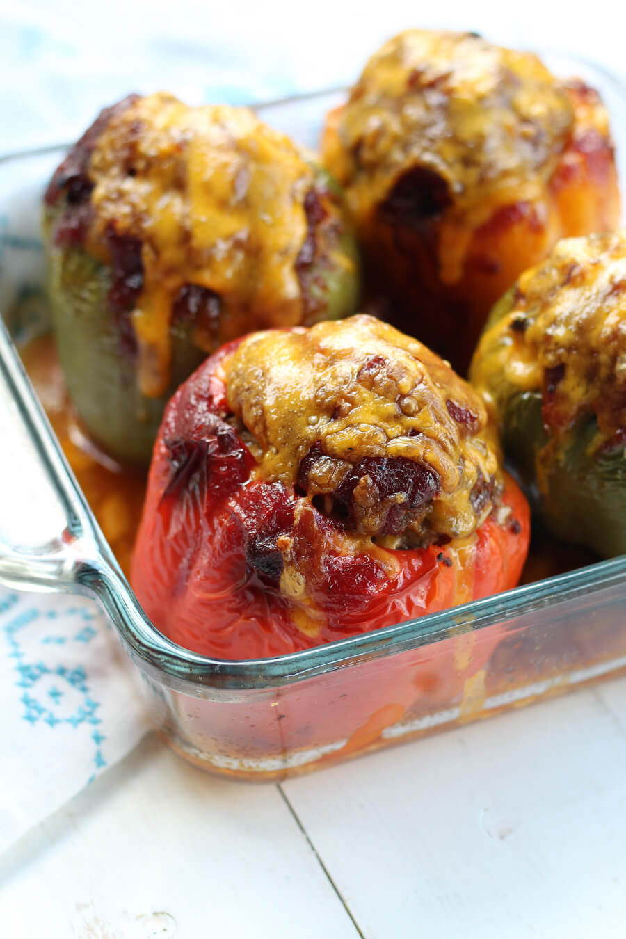 A baking dish with stuffed bell peppers topped with BBQ sauce and melted cheddar cheese