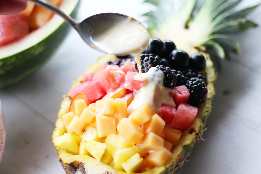 Yogurt dressing being drizzled over fruit salad in a pineapple bowl.