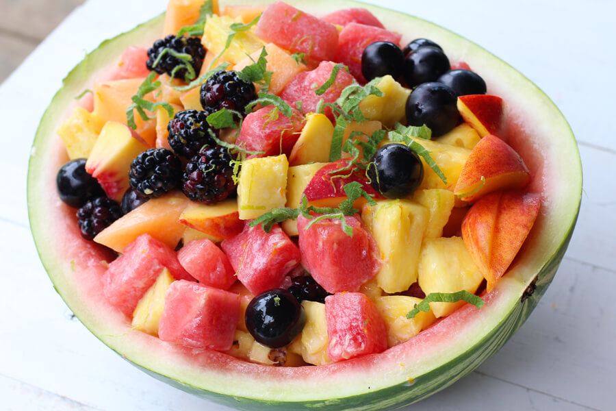 A melon full of fresh fruit salad with blackberries, watermelon, peaches and fresh mint.