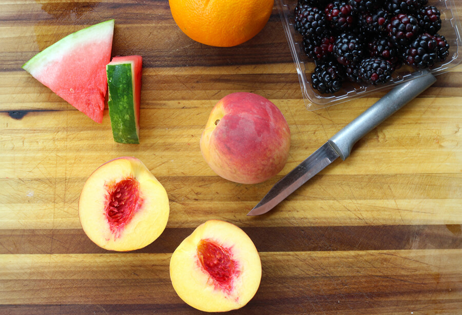 A wooden cutting board with slices of watermelon, an orange, two peaches, and blackberries