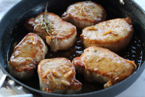 Pork Chops being fried in a skillet with sauce