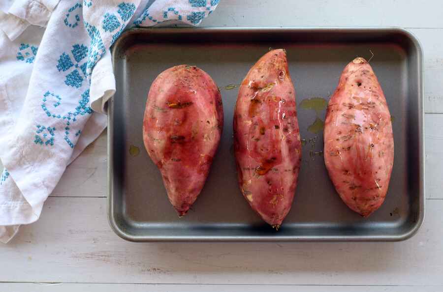 A baking sheet with three sweet potatoes drizzled with oil